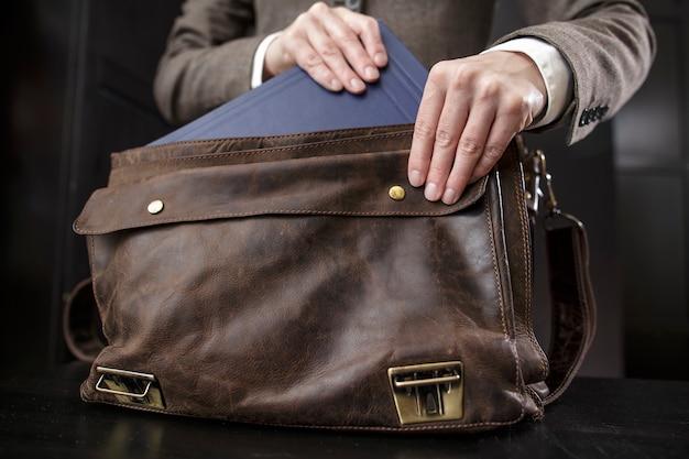Учительница в пиджаке достает книгу из старого кожаного портфеля