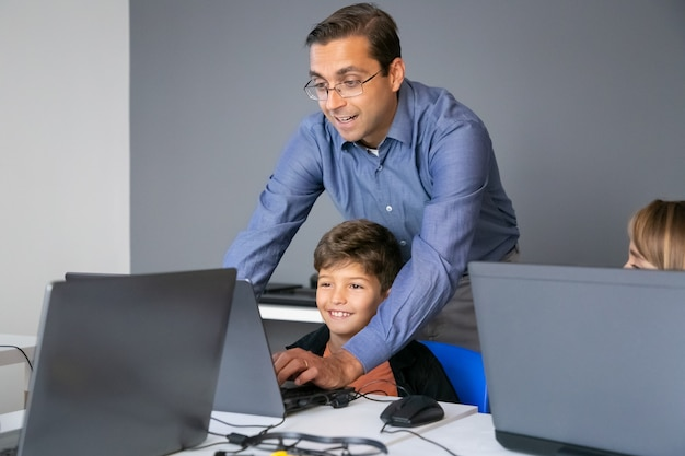 Учитель в очках объясняет урок мальчику и стоит за ним