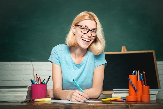 先生は緑の黒板の背景の美しい教えの上に眼鏡をかけた熟練したリーダーの若い先生です...