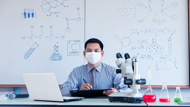 Teacher is teaching science classes online during lockdown due to covid-19 pandemic with wearing face mask