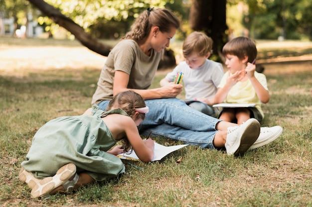 Insegnante e bambini seduti sull'erba a pieno tiro