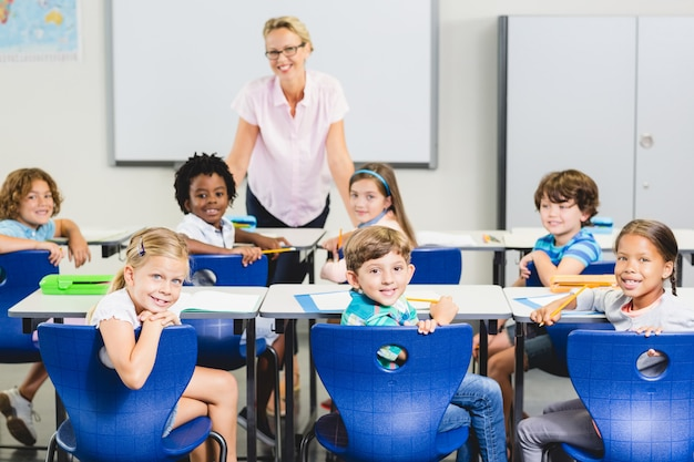Teacher and kids smiling in classroom