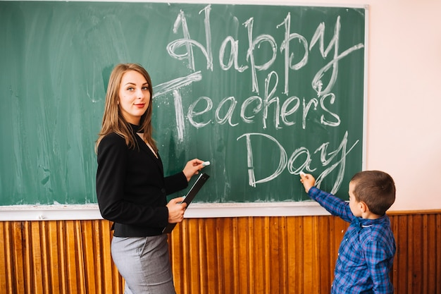 Teacher looking at camera with pupil at blackboard