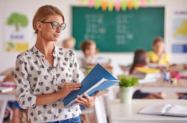 Insegnante guardando il registro scolastico