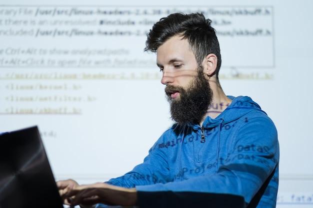 Преподаватель смотрит на ноутбук во время чтения лекций на курсах seo оптимизация бизнеса анализ контента