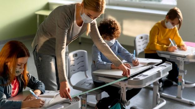 Учитель измеряет социальную дистанцию между школьными скамьями во время пандемии