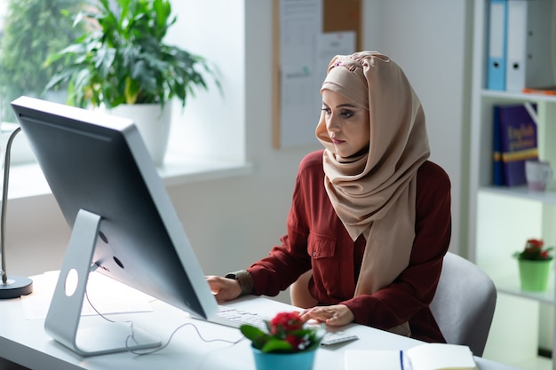 コンピューターの近くの先生。プレゼンテーションの準備中にコンピューターの前に座ってスカーフを身に着けている若い先生