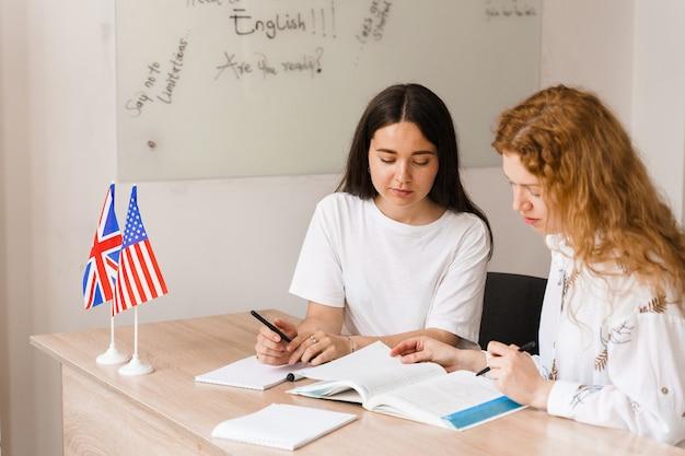 英語の先生が白いクラスの生徒に尋ねます。 2人の女子生徒が先生に答えます。グループでの作業