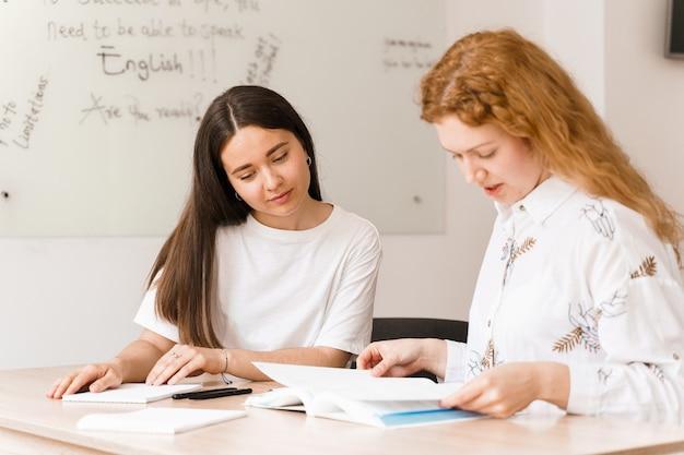 英語の先生が白いクラスの生徒に尋ねます。 2人の女子生徒が先生に答える