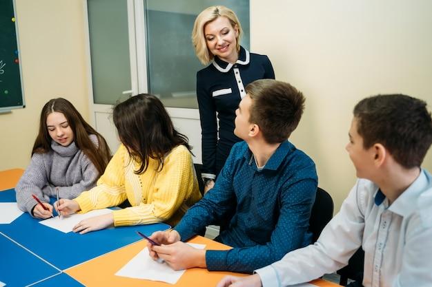Учитель английского языка объясняет урок перед учениками-подростками. образовательная концепция.