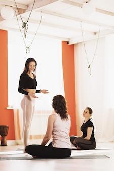 Преподаватель универсальной йоги проводит консультацию студентов в студии