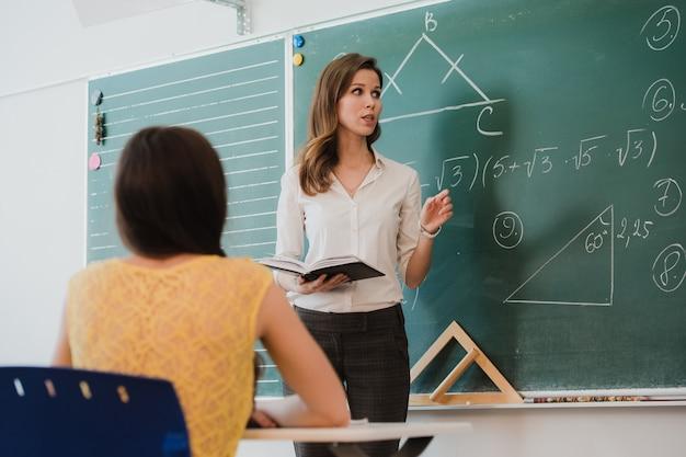Преподаватель, доцент или преподаватель проводят урок перед доской или доской листа бумаги и обучают или обучают учащихся, учеников или товарищей в школе или классе