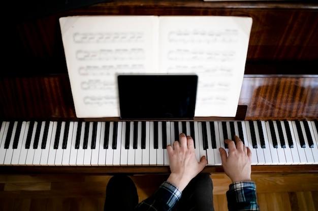 온라인 수업 중 피아노를 연주하는 교사는 태블릿을 사용하여 학생들과 의사 소통합니다.