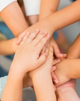 Учительница складывает руки вместе со своими учениками крупным планом