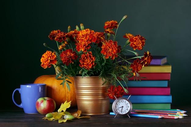 教師の日。学校に戻る。教科書、花束、学用品のある静物。
