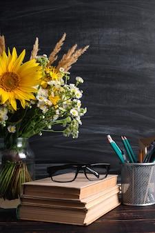 Teacher's day. black chalk board and fresh wildflowers in vase.