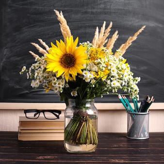 Teacher's day. black chalk board and fresh wildflowers in vase