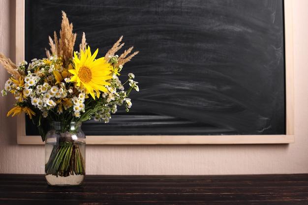 Teacher's day. black chalkboard and fresh wildflowers in vase.
