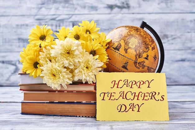 Открытка ко дню учителя и цветы. глобус и стопка книг. цени своего учителя.