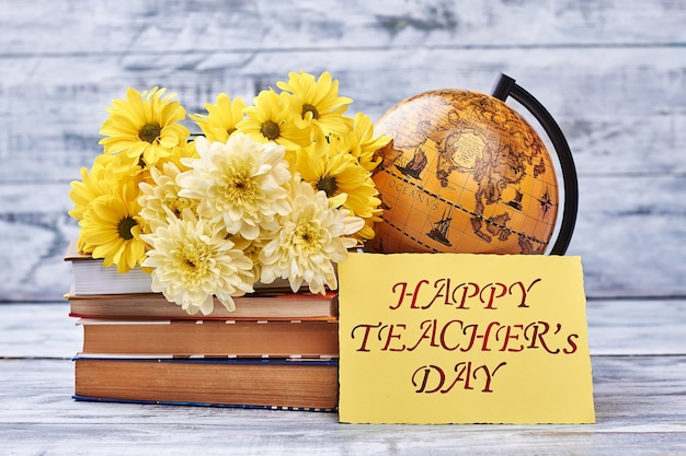 Teacher's day card and flowers. globe and stack of books. appreciate your teacher.