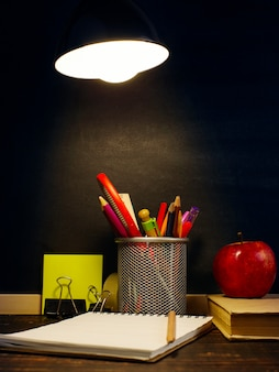 The teacher's desk on which the writing materials lie, a book and an apple, in the evening under the lamp.