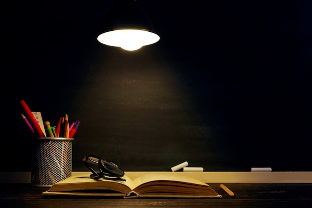 The teacher's desk on which the writing materials lie,  in the evening under the lamp.