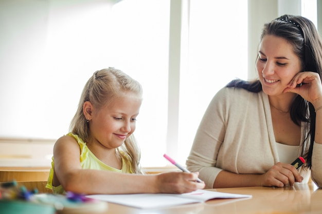 Teacher and schoolgirl sitting at table smiling