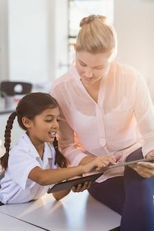 Teacher and schoolgirl using digital tablet in classroom