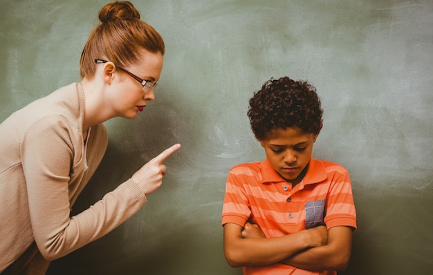 Teacher shouting at boy in classroom