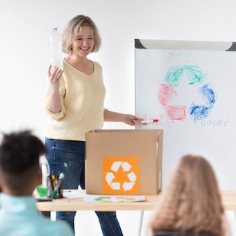 先生は子供たちにリサイクルする方法を示す
