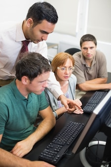 Teacher showing something on screen to mature students in the computer room