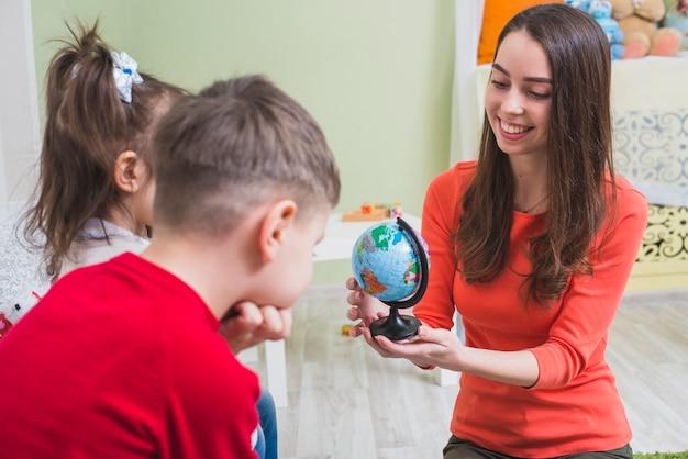 Teacher showing toy globe