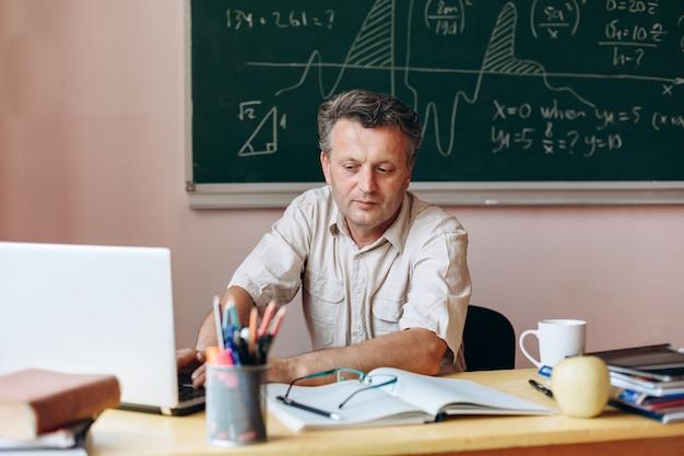 Учитель сидит за столом в классе, работает на ноутбуке