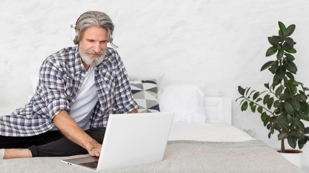 Учитель сидит на кровати, используя ноутбук