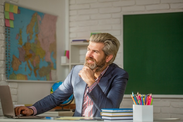 小学校の教室で微笑んでいる先生。教室で自信を持って男性教師の肖像画。クラスでラップトップを持っている若い男性教師は、教室の黒板のテーブルに座っています。