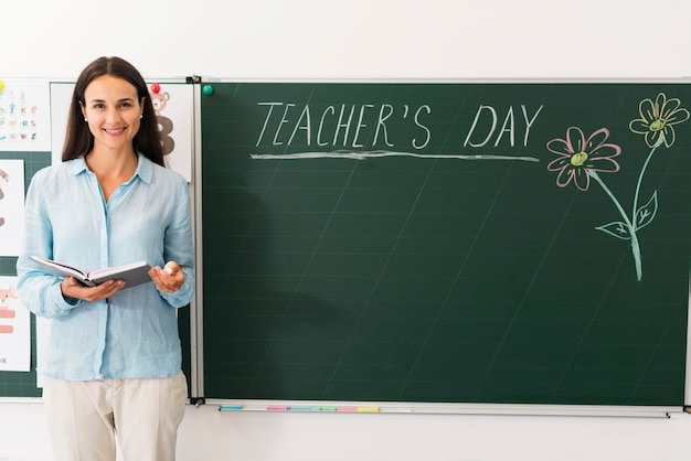 Teacher standing next to a blackboard with copy space