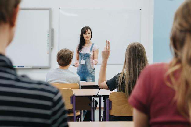10代の生徒でいっぱいの教室の前に立っている先生