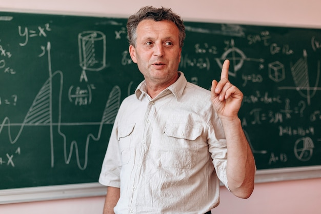 Teacher stands next the blackboard and explain a lesson holding his index finger up.