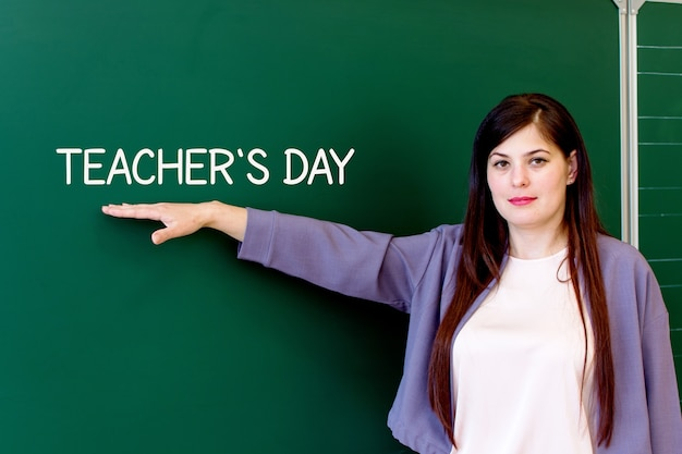 The teacher stands at the blackboard and points to the inscription teachers day