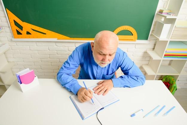 教師は知識高校の概念の教室テストでテーブルで働く教師のレッスンを開始します