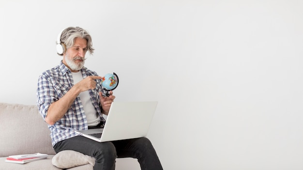 Teacher staying on couch showing earth globe at laptop
