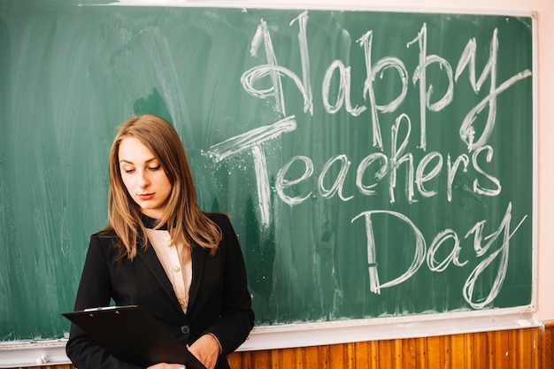 Teacher staying near chalk board