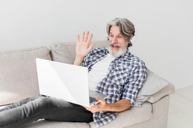 ノートパソコンで手を振っているソファに滞在している先生