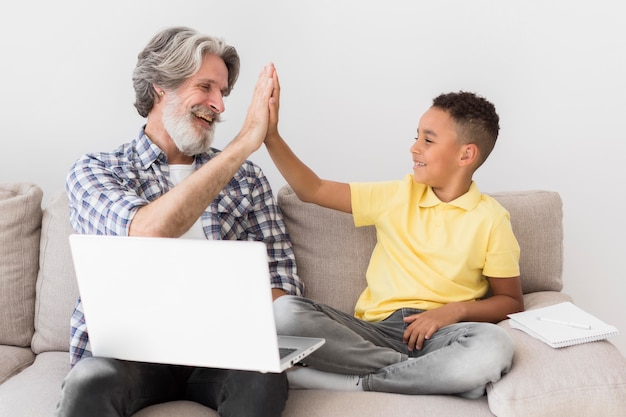 Teacher and student high fiving on couch