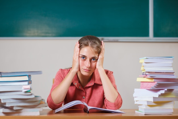 Teacher surrounded by books sitting in school classroom.