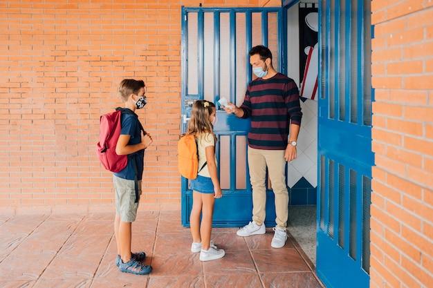 Учитель измеряет температуру детей термометром во время пандемии covid. у нее нет температуры, она здорова