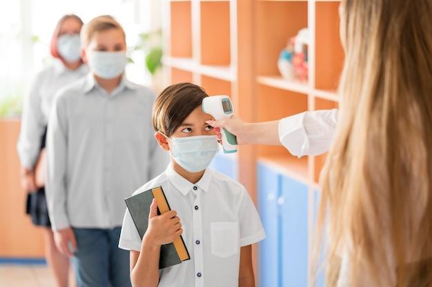 Учитель измеряет температуру тела в школе