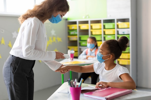 Учитель измеряет температуру ученика во время урока