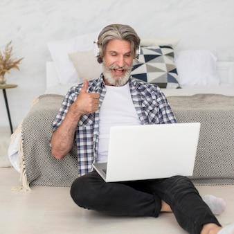 Insegnante che parla al computer portatile che si siede sul pavimento