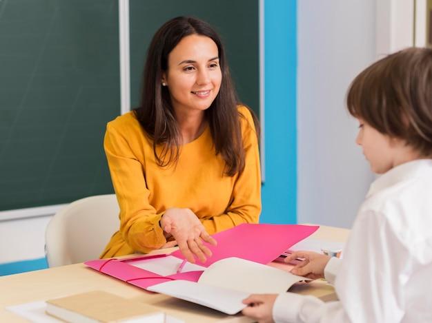 Учитель разговаривает со своим учеником в классе